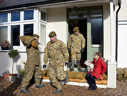 Nine year old Poppy with her dog Cosmo from Chertsey, look on as Army personnel help to shore up her home with sand bags against rising flood waters, United Kingdom, Thursday 13th February 2014. Picture by David Dyson / i-Images