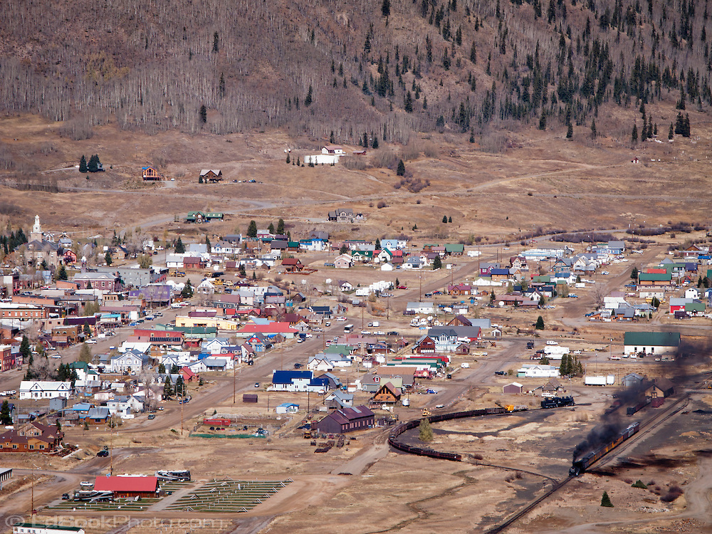 Silverton, Colorado, USA and the Animas River Valley with some mining operations visible in the distance.  The Durango & Silverton Narrow Gauge Railroad terminal is visible on the right side of the townsite. Silverton at 9305 ft elevation is the county seat of, and the only incorporated municipality in, San Juan County, Silverton is a former silver mining camp, most or all of which is now included in a federally designated National Historic Landmark District, the Silverton Historic District. .Silverton is linked to Durango by the Durango and Silverton Narrow Gauge Railroad, a National Historic Landmark. Silverton no longer has active mining, but subsists by tourism, maintenance of US 550 (which links Montrose with Durango via Silverton), mine pollution remediation, and retirees.