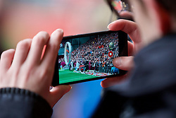 LIVERPOOL, ENGLAND - Friday, April 15, 2016: A journalists films on an Apple iPhone during the 27th Anniversary Hillsborough Service at Anfield. (Pic by David Rawcliffe/Propaganda)