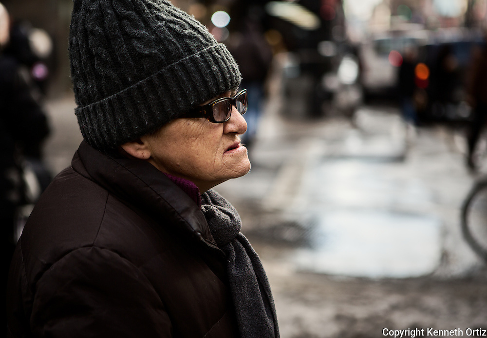 A profile shot of an elderly lady waiting to cross seventh avenue in New York City.