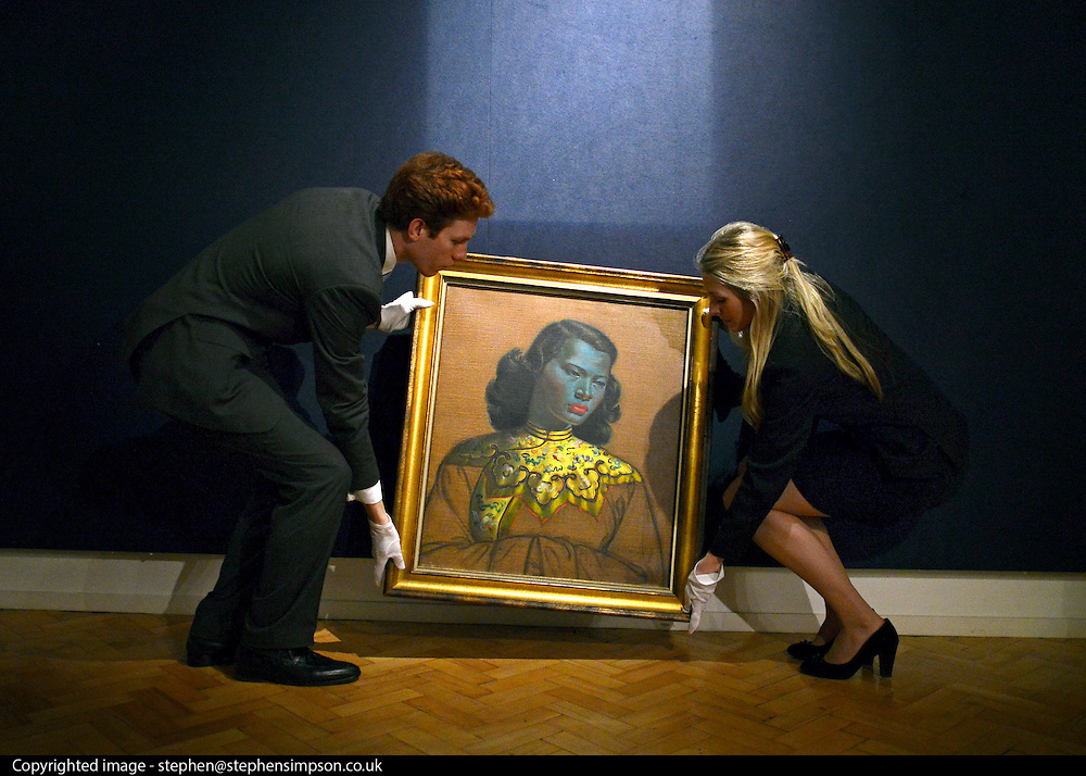 "© Licensed to London News Pictures. 18/03/2013. London, UK A gallery staff hang the painting. Press call before the auction of ""Chinese Girl"" by Vladimir Tretchikoff at Bonhams in London today 18th March 2013. The painting is said to be the most widely reproduced and recognisable painting in the world because of its wide reproduction in 1950's art prints. It is expected to fetch 300,000-500,000 GBP at auction on the 20th March. Photo credit : Stephen Simpson/LNP"