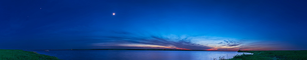 A 200&deg; panorama of the waxing crescent Moon in the spring evening twilight over Lake MacGregor in southern Alberta, on May 30, 2017. The Sun has set to the northwest at right and the Moon shines in the west. To the southwest, at left. is Jupiter and Spica.<br /> <br /> Shot from the east shore of the lake, with a 24mm lens in 8 segments, and stitched with PTGui. ACR would not stitch the leftmost segments.