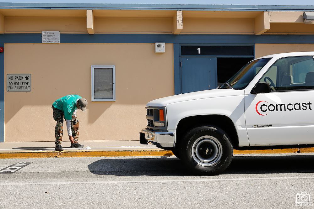 "A Comcast employee paints ""Stay Back"" in the parking lot's drop off zone with a stencil during Comcast Cares Day at Curtner Elementary School in Milpitas, California, on April 27, 2013. (Stan Olszewski/SOSKIphoto)"