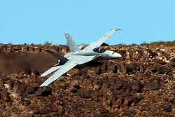 United States Navy Boeing F/A-18E Super Hornet (side 235) with an aerial refueling system ARS pod from the VFA-122 Flying Eagles squadron flies low level on the Jedi Transition through Star Wars Canyon / Rainbow Canyon, Death Valley National Park, Panamint Springs, California, United States of America