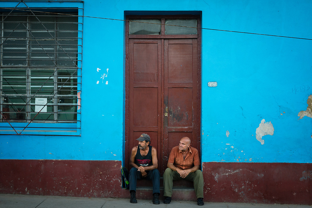 Two men sitting in doorway of a colourful building in Trinidad, Cuba