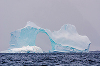 Sculpted ice arch on a tabular iceberg grounded in Pleneau Bay near Port Charcot, Antarctica.