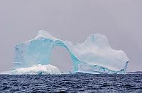 Sculpted ice arch on a tabular iceberg grounded in Pleneau Bay near Port Charcot, Antarctica.