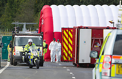 © London News Pictures. 11/09/2012. Hindhead, UK . Police and forensics at the scene of a fatal bus crash on the north bound A3 motorway near Hindhead Tunnel, Hindhead, Surrey on September 11, 2012.Three people were killed and a number of others seriously injured when a coach carrying overturned after crashing into a tree. Photo credit: Ben Cawthra/LNP