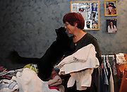 SUN-STAR PHOTO BY BEA AHBECK<br /> After putting the children to bed, Renate gets a snuggle from a family cat while folding laundry in their Atwater home on Nov. 15, 2010. The walls in the room are covered with pictures of her daughter Mona.