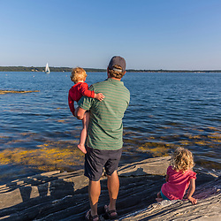 A man and his young kids explore the shoreline on East Gosling Island in Casco Bay, Harpswell, Maine.