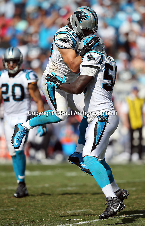 Carolina Panthers outside linebacker A.J. Klein (56) leaps and celebrates with Carolina Panthers outside linebacker Thomas Davis (58) after Klein intercepts a fourth quarter pass in Houston Texans territory during the 2015 NFL week 2 regular season football game against the Houston Texans on Sunday, Sept. 20, 2015 in Charlotte, N.C. The Panthers won the game 24-17. (©Paul Anthony Spinelli)