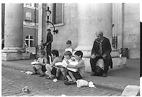 Hungry homeless man looking at group of young boys eating pizza out of the box, Covent Garden, London street photography in 1982. Tri-X