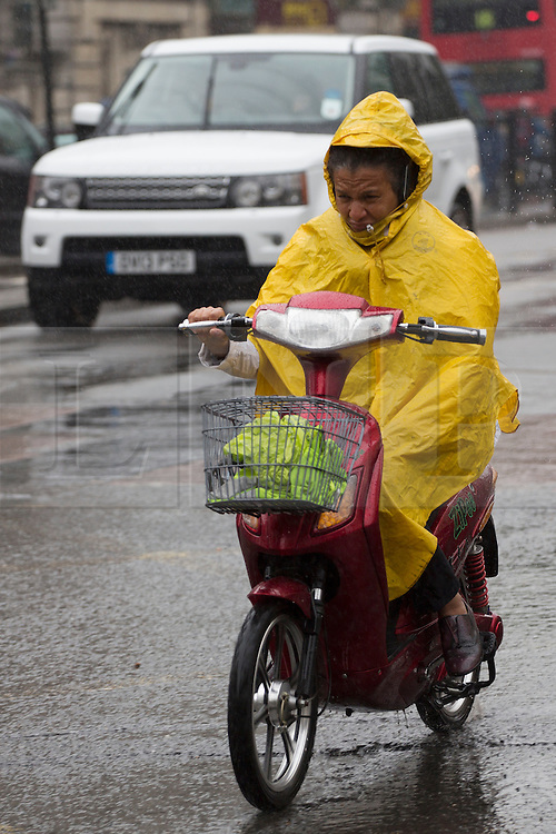 © licensed to London News Pictures. London, UK 09/09/2013. A man ride a scooter under the rain in central London on Monday, September 9, 2013. Photo credit: Tolga Akmen/LNP