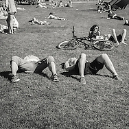 People relaxing and enjoying the sun in the park garden by lille lungegardsvatnet in Bergen Norway