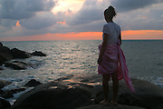 A young female traveler wrapped in a pink bed sheet, with her hair up watches the sun rise from Hat Yuan Beach, Koh Phangnan, Thailand