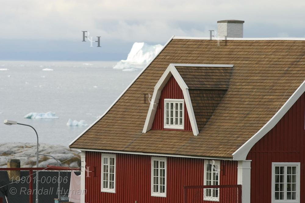 Danish-style wooden building overlooks Disko Bay iceberg at Ilulissat, third largest town in Greenland.