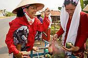 13 MARCH 2006 - CHAU DOC, AN GIANG, VIETNAM: A vendor sells fruit to a Cham woman wearing a Moslem head scarf in a village near Chau Doc, Vietnam in the Mekong delta. The Cham are one of the largest ethnic minorities in southern Vietnam. Most Vietnamese are Buddhists, but the Cham are Moslem. The Mekong is the lifeblood of southern Vietnam. It is the country's rice bowl and has enabled Vietnam to become the second leading rice exporting country in the world (after Thailand). The Mekong delta also carries commercial and passenger traffic throughout the region.  Photo by Jack Kurtz