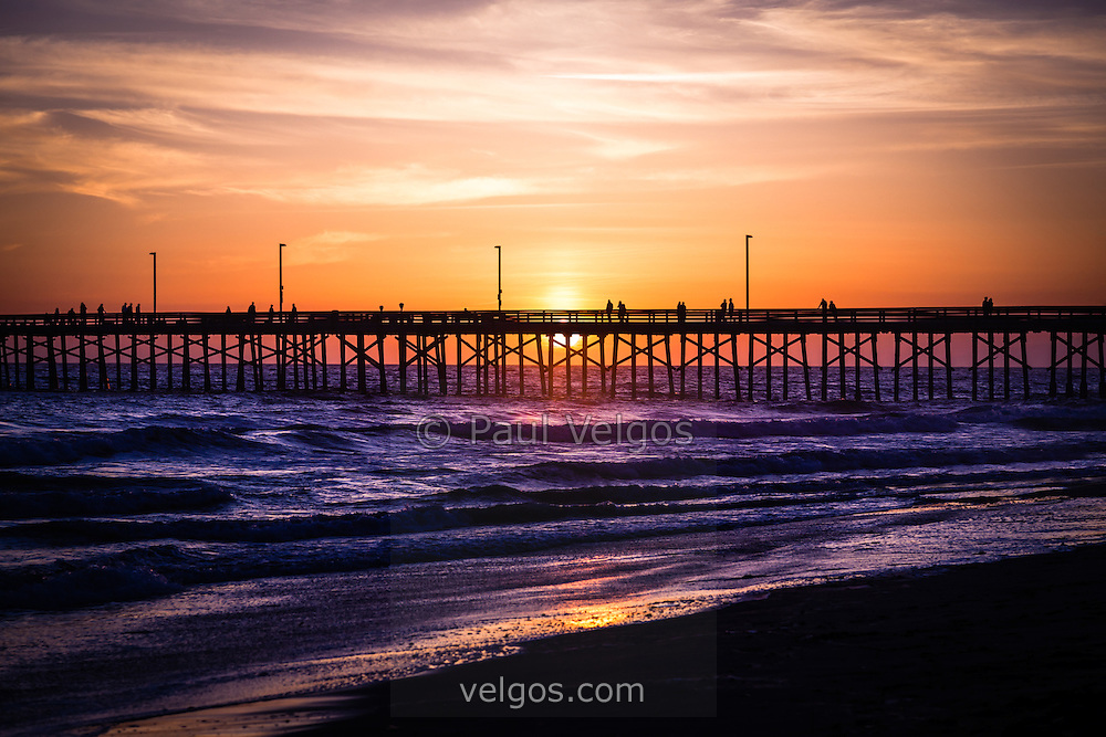 Photo of Newport Pier sunset in Newport Beach California. Newport Beach is a wealthy beach community along the Pacific Ocean in Orange County California. Photo is high resolution and was taken in 2012.