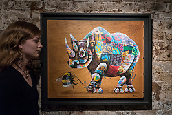"© Licensed to London News Pictures. 24/05/2018. LONDON, UK. London, UK.  24 May 2018. An assistant views a painting of a Southern white rhino at the preview of ""Missing"" an exhibition by artist and environmentalist Louis Masai at the Crypt Gallery in Euston.  The exhibition features sculptures, installations and paintings depicting 20 endangered species across the world from the South African penguin to the humble bumble bee.  The show runs 25 to 27 May 2018. Photo credit: Stephen Chung/LNP"