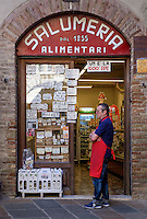 SAN GIMIGNANO, ITALY - CIRCA MAY 2015:  Merchant standing in front of typical store in the medieval walled city of San Gimignano in Tuscany