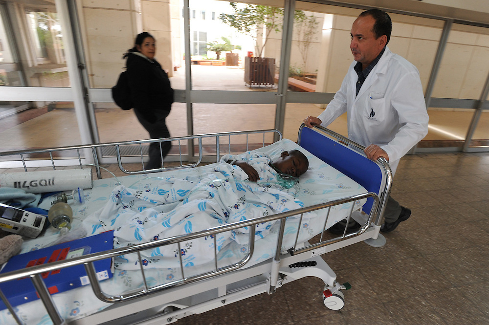 Dr. Sion Huri, Head of Pediatric Intensive Care Unit in Wolfson Medical Center takes Woodley Elysee, a six-year-old Haitian boy to the Intensive Care Unit, soon after he has undergone a catheterization procedure on February 03, 2010. Woodley was brought to Israel by the IDF aid mission force. Woodley's treatment is arranged by the Israeli humanitarian organization Save A Child's Heart which provides life saving surgeries for children from developing countries.