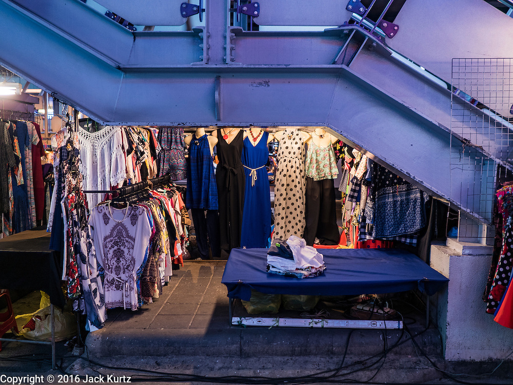 26 MAY 2016 - BANGKOK, THAILAND: A dress shop under the stairs that lead to the BTS Sala Daeng Skytrain station in the Silom Road night market. The night market on Silom Road, close to Bangkok's famous Patpong tourist area, is being closed by the Bangkok municipal government. Vendors have been told they have to leave the sidewalk on Silom Road by the end of May, 2016. The market is the latest street market being shut down by city officials as a part of the government's plan to clean up Bangkok. The Silom Road night market sells mostly tourist oriented clothes, inexpensive Thai art, and bootleg movies on DVD.       PHOTO BY JACK KURTZ