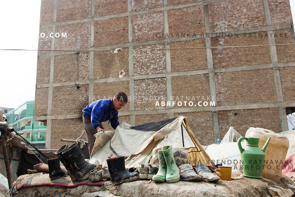 A young boy builds a tent on top of his mud brick house in a refugee camp