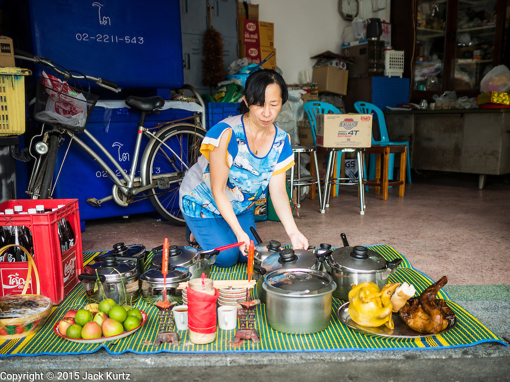 28 AUGUST 2015 - BANGKOK, THAILAND:  A woman leaves out a banquet of food for her ancestors on Hungry Ghost Day in Bangkok's Chinatown. Mahayana  Buddhists believe that the gates of hell are opened on the full moon of the seventh lunar month of the Chinese calendar, and the spirits of hungry ghosts allowed to roam the earth. These ghosts need food and merit to find their way back to their own. People help by offering food, paper money, candles and flowers, making merit of their own in the process. Hungry Ghost Day is observed in communities with a large ethnic Chinese population, like Bangkok's Chinatown.     PHOTO BY JACK KURTZ