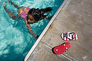 A young girl swims as patriotic sandals sit atop the deck during the Waving the Red, White & Blue Pool Party at the Milpitas Sports Center in Milpitas, California, on July 4, 2014. (Stan Olszewski/SOSKIphoto)