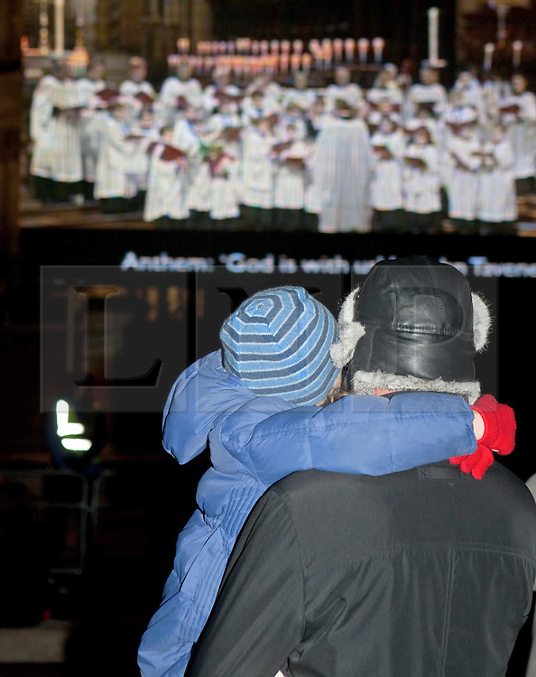 ©London News Picures.. Office workers and shoppers stop to watch the first live screening of St Paul's Christmas carol service in Paternoster Square. A 25m screen was set up in Paternoster square. Photo credit should read Fuat Akyuz/London News Pictures.
