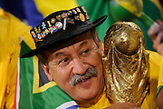 A fan of Brazil with a replica of the World Cup trophy..