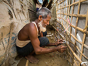 07 NOVEMBER 2014 - SITTWE, RAKHINE, MYANMAR: A Rohingya Muslim man repairs his tent in an IDP camp for Rohingya Muslims near Sittwe. After sectarian violence devastated Rohingya communities and left hundreds of Rohingya dead in 2012, the government of Myanmar forced more than 140,000 Rohingya Muslims who used to live in and around Sittwe, Myanmar, into squalid Internal Displaced Persons camps. The government says the Rohingya are not Burmese citizens, that they are illegal immigrants from Bangladesh. The Bangladesh government says the Rohingya are Burmese and the Rohingya insist that they have lived in Burma for generations. The camps are about 20 minutes from Sittwe but the Rohingya who live in the camps are not allowed to leave without government permission. They are not allowed to work outside the camps, they are not allowed to go to Sittwe to use the hospital, go to school or do business. The camps have no electricity. Water is delivered through community wells. There are small schools funded by NOGs in the camps and a few private clinics but medical care is costly and not reliable.   PHOTO BY JACK KURTZ