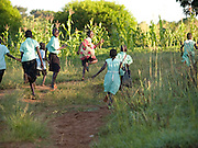 Children from Florence's family heading off to school. Before her training with Send a Cow some of the children weren't able to attend school because of a lack on school fees.