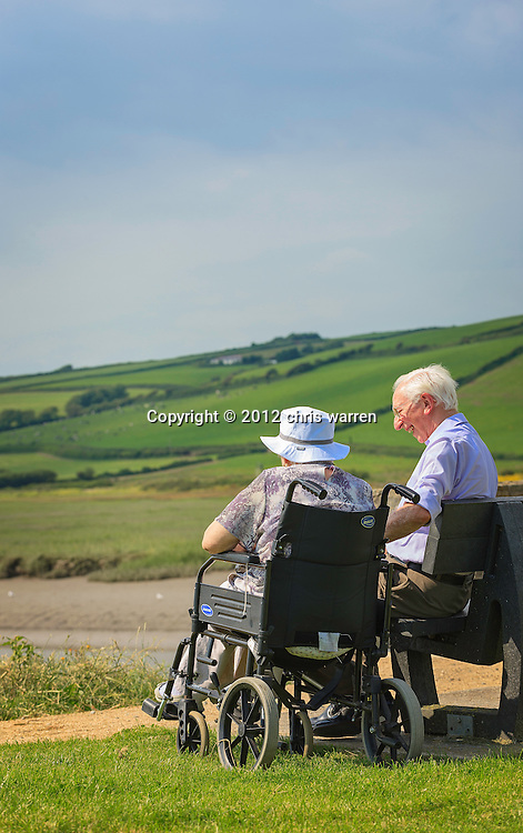 Senior couple - female wheelchair user and male - enjoying view out to sea from Kidwelly Quay<br /> Gwendraeth Valley<br /> Carmarthenshire<br /> Valleys<br /> South<br /> Walking<br /> Activities and Sports