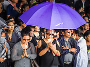 19 OCTOBER 2014 - BANG BUA THONG, NONTHABURI, THAILAND: Mourners stand under an umbrella during a rain storm at Apiwan Wiriyachai's cremation at Wat Bang Phai in Bang Bua Thong, a Bangkok suburb, Sunday. Apiwan was a prominent Red Shirt leader. He was member of the Pheu Thai Party of former Prime Minister Yingluck Shinawatra, and a member of the Thai parliament and served as Yingluck's Deputy Prime Minister. The military government that deposed the elected government in May, 2014, charged Apiwan with Lese Majeste for allegedly insulting the Thai Monarchy. Rather than face the charges, Apiwan fled Thailand to the Philippines. He died of a lung infection in the Philippines on Oct. 6. The military government gave his family permission to bring him back to Thailand for the funeral. His cremation was the largest Red Shirt gathering since the coup.     PHOTO BY JACK KURTZ