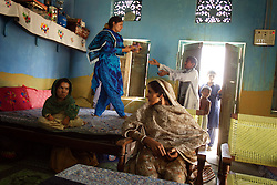 Mukhtar Mai, 33, sits in her living room with friends and family members, Meerwala, Pakistan, April 27, 2005. Mai, went against the Pakistani tradition of committing suicide when she brought charges against the men who gang raped her nearly three years ago. With money from the ruling she opened two schools, one for girls, the other for boys, which provides education to at least two sons and one nephew from the rapists' family. Mai cited that education is the only thing that will stop such acts from happening.