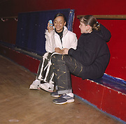 Teenage girls laughing, one of them holding a mobile phone, Cardiff, 2000's