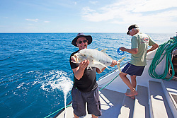 A tourist holds his catch on a charter boat in Camden Sound.