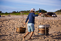 Woman carrying baskets of fish on the China Beach, Vietnam.