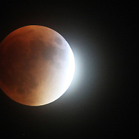 With direct sunlight bouncing off the right side of the moon and Earth's shadow dimming the left, a lunar eclipse nears totality in the cloudy skies Sunday night over Mount Pleasant. (ANDREW KNAPP/STAFF)