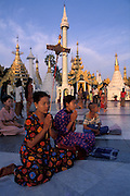Pilgrims sit in prayer amongst the various mini-stupas surrounding Schwedagon Paya.<br />