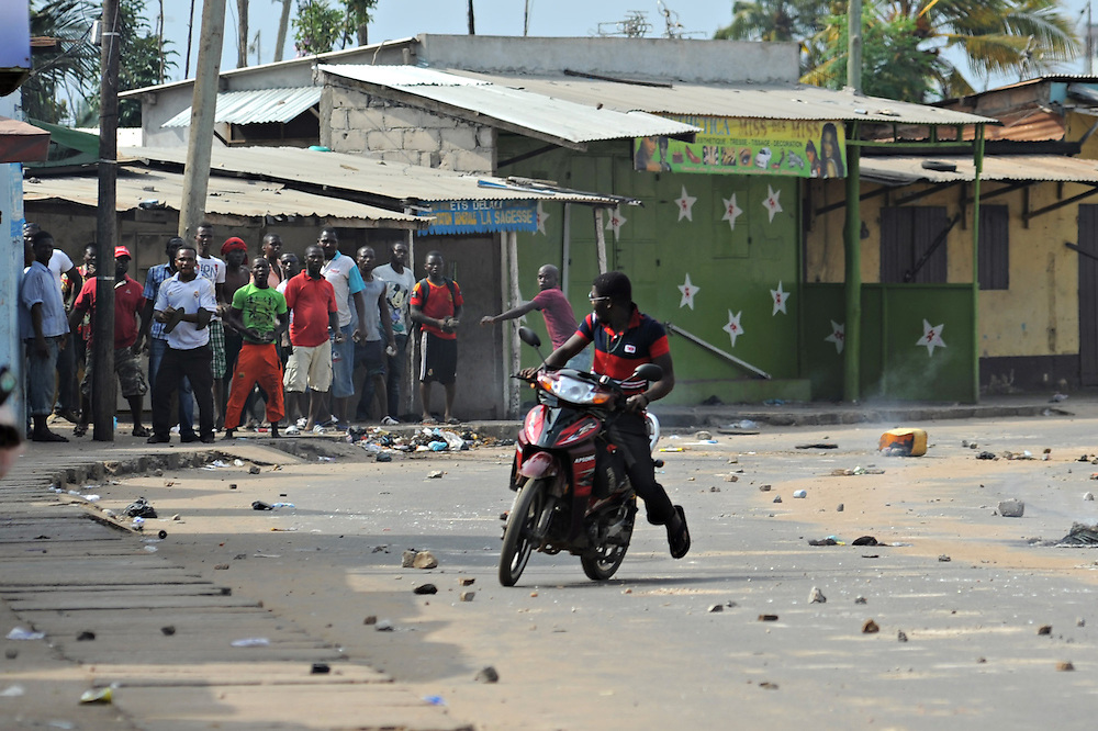 LOME, TOGO - 12-10-05   - A motorcyclist attempts to avoid stones thrown by protesters as they clashed with police in Lomé on October 5. A peaceful protest was scheduled by opposition groups, but their route was blocked by police.  For months, opposition parties have been calling for the departure of president Faure Gnassingbe, whose family has been in power for over 40 years.   Photo by Daniel Hayduk