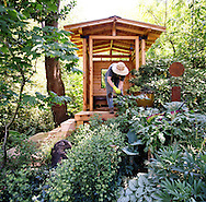 Woman gardener outside with shade plants and pavilion