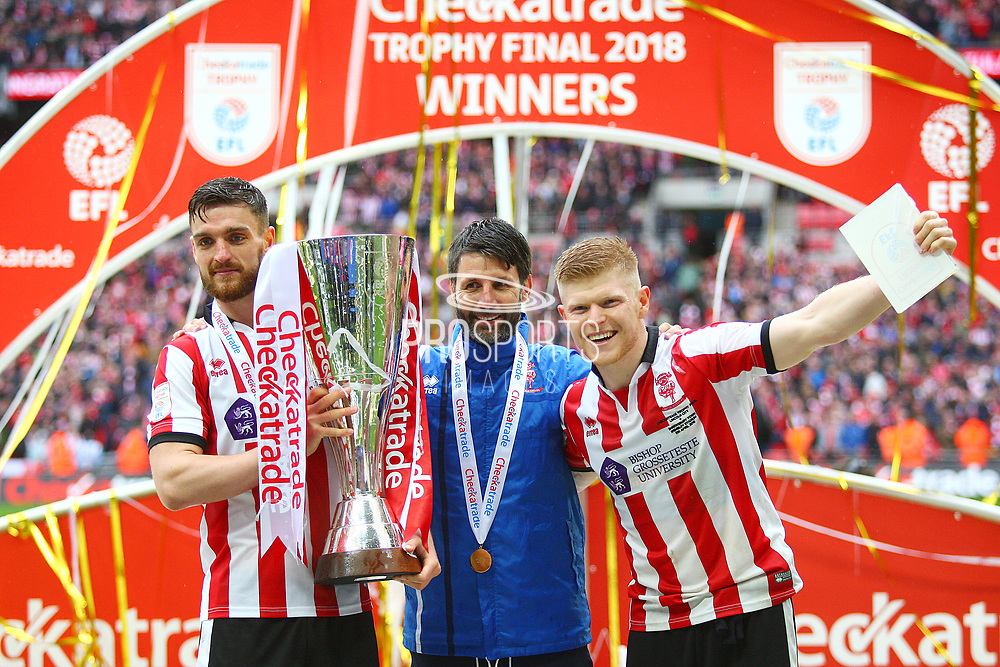 Lincoln City's match winner Elliott Whitehous and Lincoln City's Luke Waterfall  lift the Checkatrade Trophy with Lincoln City manager Danny Cowley during the EFL Trophy Final match between Lincoln City and Shrewsbury Town at Wembley Stadium, London, England on 8 April 2018. Picture by John Potts.