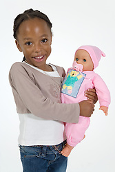 Young girl holding a toy doll,
