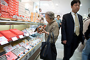 elderly woman counting her money while shopping Japan