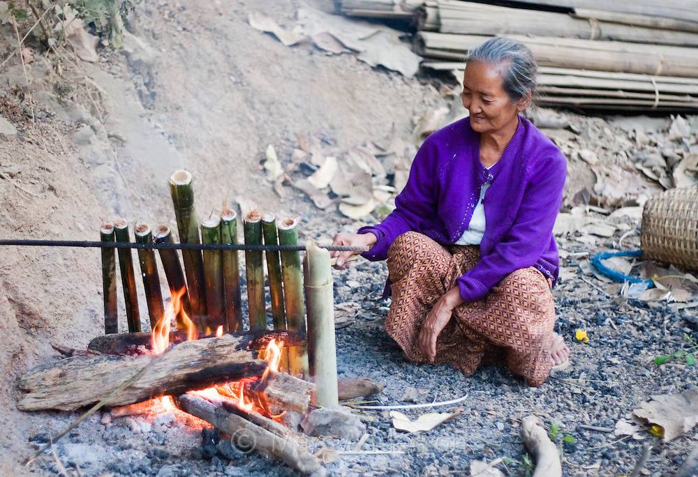 Old woman using bamboo poles to cook over an open fire in  Mae Sam Laep, a Burmese refugee settlement in Mae Hong Son Province, Thailand