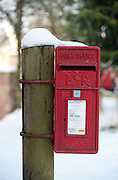 A red UK Royal Mail post box attached to a wooden post in the snow.