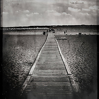 A long wooden jetty on a beach with a group of people in the distance