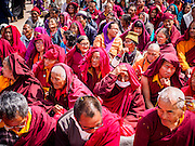 07 MARCH 2017 - KATHMANDU, NEPAL: Buddhist monks and lay people sit around Boudhanath Stupa during the consecration ceremony. Boudhanath Stupa, the most important Buddhist site in Nepal and a popular tourist attraction, was consecrated Tuesday in a ceremony attended by thousands of Buddhist monks and Buddhist people from Nepal and Tibet. The stupa was badly damaged in the 2015 earthquake that devastated Nepal. The stupa, which reopened in November 2016, was repaired in about 18 months. The repair was financed by private donations raised by international Buddhist organizations.     PHOTO BY JACK KURTZ